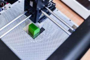 3D Drucker beim 3D Druck eines simplen grünen Würfels